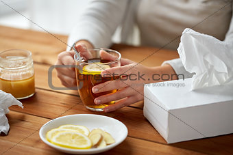 close up of ill woman drinking tea with lemon