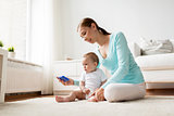 happy mother showing smartphone to baby at home