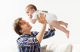 happy young father playing with baby at home