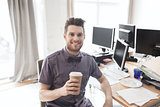 happy creative male office worker drinking coffee