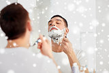 man shaving beard with razor blade at bathroom