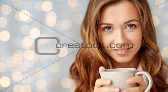 close up of happy woman with tea cup over lights