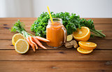 glass jug of carrot juice, fruits and vegetables