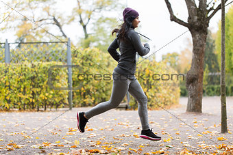 close up of young woman running in autumn park