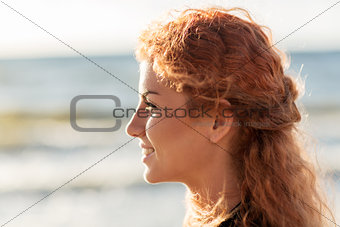happy young redhead woman face on beach