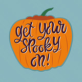 Orange pumpkin with Halloween text on blue background
