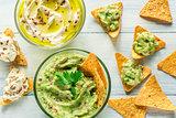 Bowls of hummus and guacamole with tortilla chips