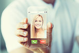 close up of hand with incoming call on smartphone