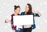 smiling teenage girls holding white blank board