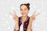 happy teenage girl showing peace sign over snow