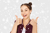happy teenage girl showing thumbs up over snow