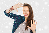 smiling teenage girl showing hands over snow