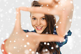 teenage girl making frame of fingers over snow