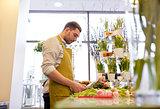 smiling florist man making bunch at flower shop