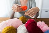 woman pulling yarn up into ball