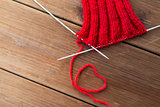knitting needles and thread in heart shape on wood