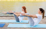 women making yoga in half-boat pose outdoors