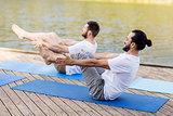 men making yoga in half-boat pose outdoors