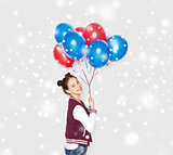 happy teenage girl with helium balloons over snow