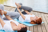 women making yoga in supine pigeon pose outdoors