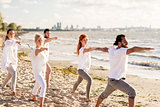 people making yoga in warrior pose on beach