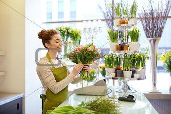 smiling florist woman making bunch at flower shop