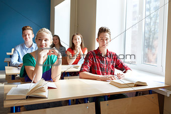 group of students with books at school lesson