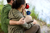 happy couple with cups drinking in nature