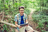 happy man with backpack and tablet pc in woods