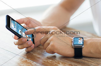 close up of hands with smart phone and watch