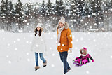 happy family with sled walking in winter forest