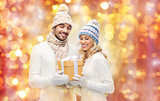 smiling couple in winter clothes with gift box