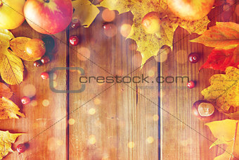 frame of autumn leaves, fruits and berries on wood