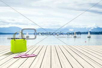 green bag on a wooden jetty with sailing boats in the background