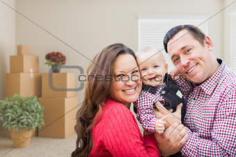 Caucasian Family with Baby In Room with Moving Boxes