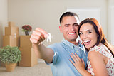 Young Military Couple with House Keys in Empty Room with Packed