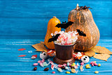 Halloween composition with pumpkins, candy bucket, paper bats, r