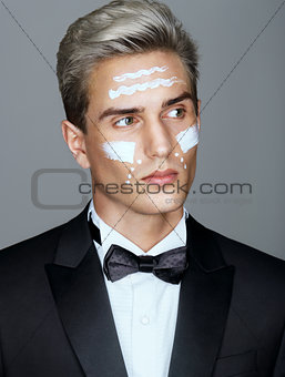 Beautiful face of imposing man with cosmetic cream on cheeks, spa treatment