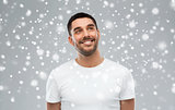 smiling man looking up over snow background