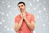 young man touching his face over snow background