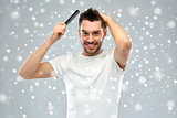 happy man brushing hair with comb over snow