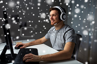man in headset playing computer video game at home