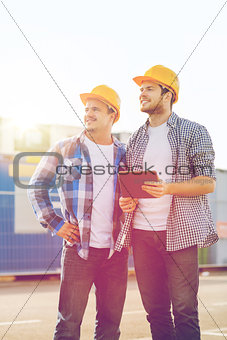 smiling builders with tablet pc outdoors