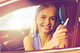 happy woman getting car key in auto show or salon