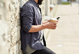 man with smartphone drinking coffee on city street