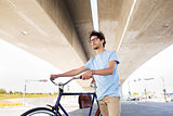 hipster man with fixed gear bike under bridge