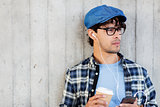 man with earphones and smartphone drinking coffee