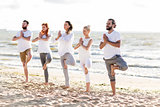 people making yoga in tree pose on summer beach