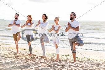 people making yoga in tree pose on summer beach