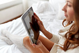 young woman with tablet pc in bed at home